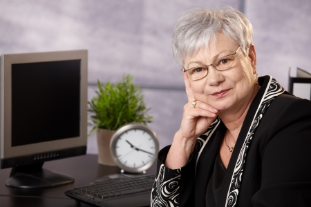 Portrait of senior businesswoman sitting at desk in office, looking at camera. photo