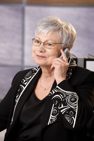 old cell phone: Senior businesswoman on mobile phone call, smiling.