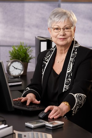 Portrait of senior businesswoman working with computer at desk in office, looking at camera, smiling. photo