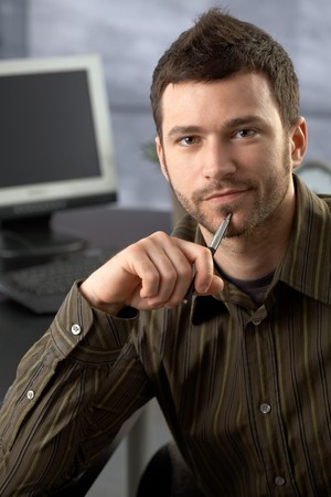 Portrait of confident businessman sitting in office, holding pen, looking at camera. photo