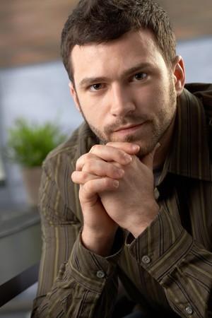 cabello casta�o claro: Retrato de hombre determinado mirando la c�mara sentado con las manos dobladas en la Oficina.