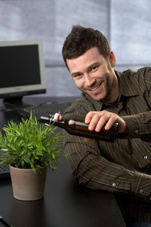 Funny young businessman pretending to water potted plant from beer bottle in office. photo