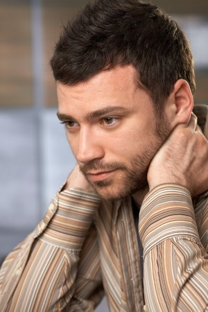 offish: Young handsome man sitting with hands on neck looking thoughtful and concentrating.