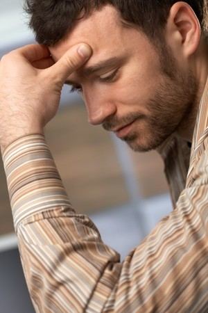 holding the head: Portrait of young man in trouble, holding head looking down. Stock Photo