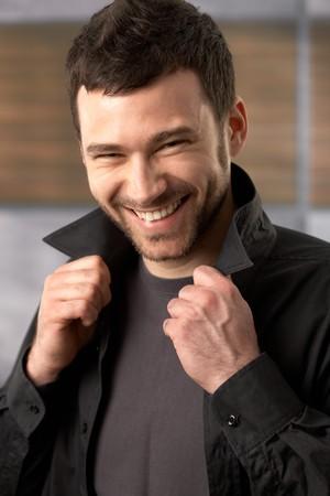 Trendy young man laughing at camera posing in stylish shirt. photo
