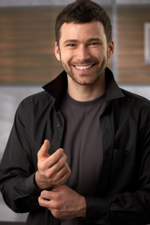 Happy trendy man posing in black shirt doing the button.