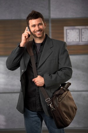 Happy office worker standing in lobby holding laptop bag talking on mobile phone smiling. Stock Photo