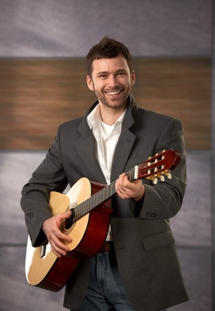 Portrait of trendy young guy smiling playing guitar. photo