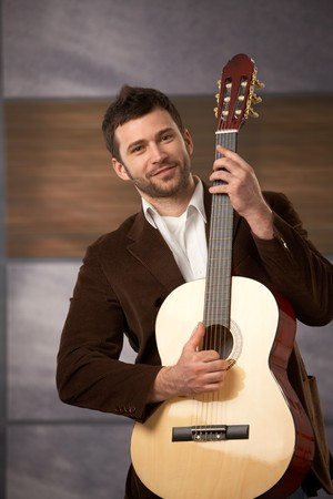 Handsome stylish guy standing holding guitar, smiling at camera. photo