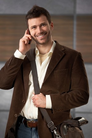 Young stylish office worker standing with laptop bag, smiling, talking on mobilephone. Stock Photo - 7082954