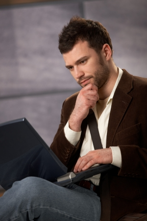 Thoughtful guy sitting with laptop computer in lap, looking serious. Stock Photo