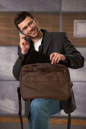 Happy office worker talking on mobilephone, taking computer out of laptop bag, smiling.