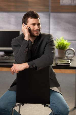 Trendy young businessman sitting on chair in office, talking on mobile phone, smiling. photo