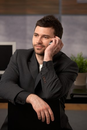 Portrait of young confident businessman listening to mobile phone call, smiling. Stock Photo - 7082794