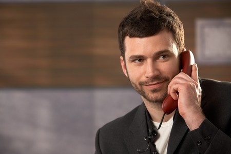 Portrait of smiling businessman on landline phone call in office. photo