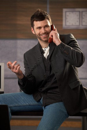 Happy businessman laughing making landline phone call, gesturing with hand, sitting on office desk. photo