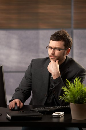 severity: Young businessman wearing glasses concentrating on computer work in office.