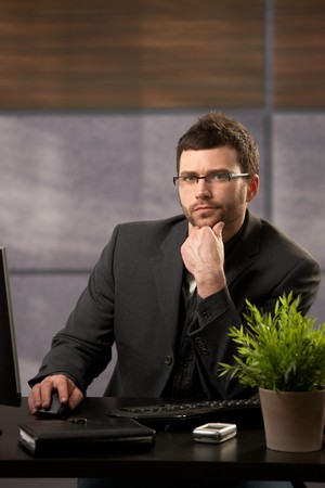 offish: Portrait of serious businessman looking at camera, sitting at desk in office. Stock Photo