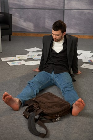 Trendy office worker sitting on office floor bare feet, surrounded with papers, documents and  laptop bag. photo