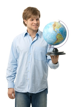 Young man thinking on next holiday holding globe in hand, smiling. Isolated on white. Stock Photo - 7129929