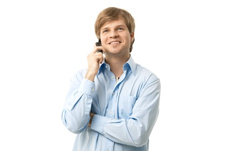 Smiling young man, wearing blue shirt, talking on mobile. Cutout. Stock Photo - 7129857
