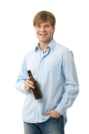 Casual young man holding bottle of beer, smiling. Isolated on white. photo