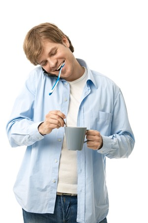 Happy man with toothbrush in his mouth, holding cup of tea talking on mobile. Isolated on white. Stock Photo - 7129893
