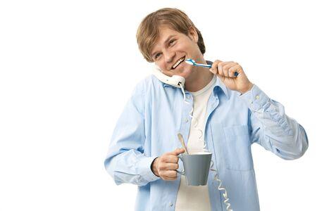 Happy man talking on phone while brushing teeth. Isolated on white. photo