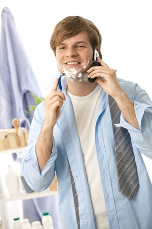 Young man talking on mobile while shaving. Isolated on white. Stock Photo - 7130132