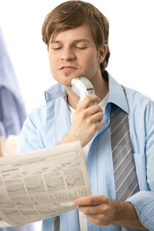 Young man shaving with electric razor, reading newspaper. Isolated on white photo