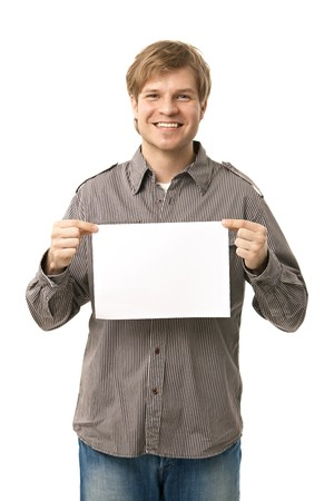 Casual young man holding blank sheet of paper, smiling. Isolated on white. photo