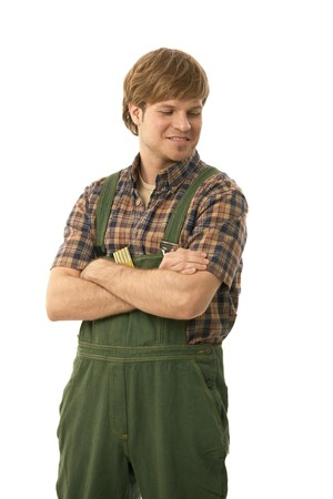 Portrait of young handyman wearing green workwear. Isolated on white. photo