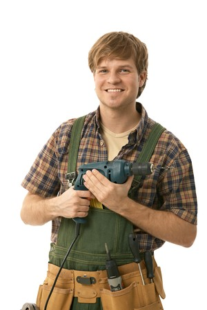 Young handyman holding power drill, smiling. Isolated on white.