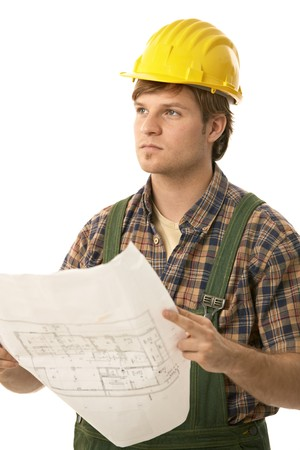 Young builder wearing hardhat, holding floor plan, looking ahead. Isolated on white. photo
