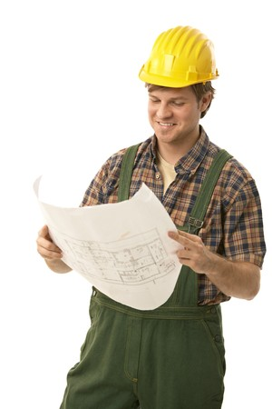 Confident handyman wearing hardhat, holding floor plan, smiling. Isolated on white. photo