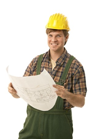 Happy builder wearing hardhat, holding floor plan, looking at camera. Isolated on white. Stock Photo - 7129892