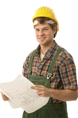 Confident handyman wearing workwear, holding floor plan, looking at camera. Isolated on white. photo