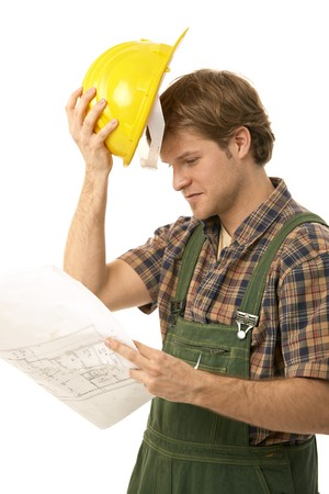 Young builder looking at floor plan, holding his hardhat. Isolated on white. photo