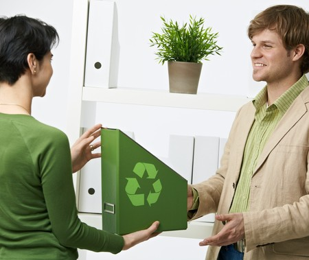 Happy office workers holding green folder with recycling symbol. photo