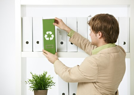 environmentalism: Man drawing out green folder with recycling symbol in office. Stock Photo