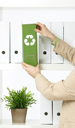 Conceptual image of environmental conservation, businessman holding green folder with recycling symbol. photo