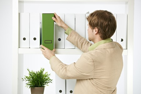 environmentalist: Young environmentalist in office holding green folder. Stock Photo