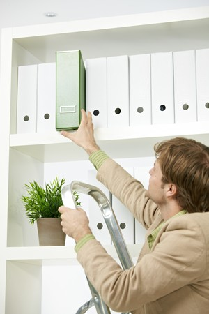 Businessman on ladder removing green folder from shelf. photo