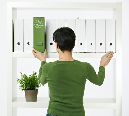 Conceptual image of environmental conservation, woman working in green office. photo