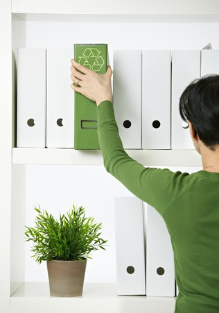 environmentalism: Female office worker choosing green folder with recycling symbol.