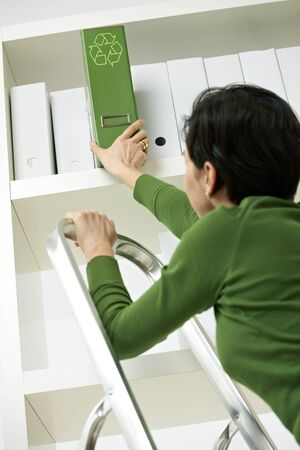 Office worker on ladder removing green folder with recycling symbol from shelf. photo