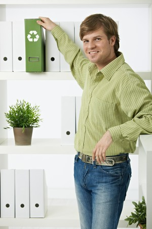 environmentalist: Young environmentalist man standing in office pulling out green folder,  Stock Photo