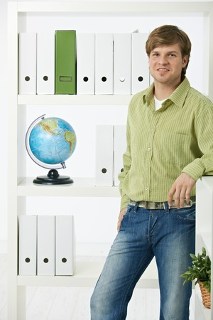 environmentalist: Young environmentalist man standing in office looking at camera, smiling. Stock Photo