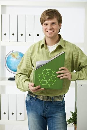 logo reciclaje: Trabajador de oficina joven feliz celebraci�n de carpeta verde con logotipo de reciclaje. Foto de archivo