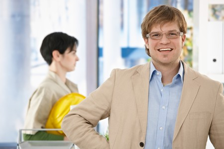Portrait of happy young architect standing in office, colleague walking in background. Stock Photo - 7129927